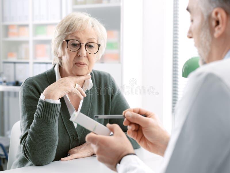 Medico professionista che dà una medicina di prescrizione ad un paziente senior fotografia stock libera da diritti