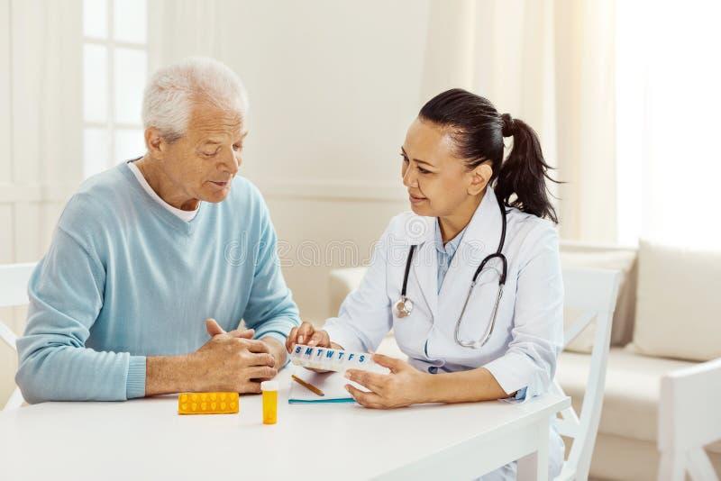 Medico professionista piacevole che tiene una scatola con le pillole immagine stock libera da diritti