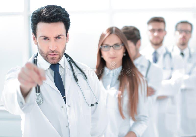 Medico rigoroso, indicando voi, stante nel posto di lavoro fotografia stock libera da diritti