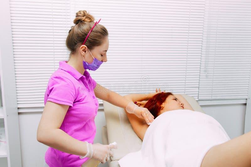 Medico rimuove i capelli dalla ragazza sulle ascelle Zuccherando nel salone Inceratura delle ascelle della donna fotografia stock