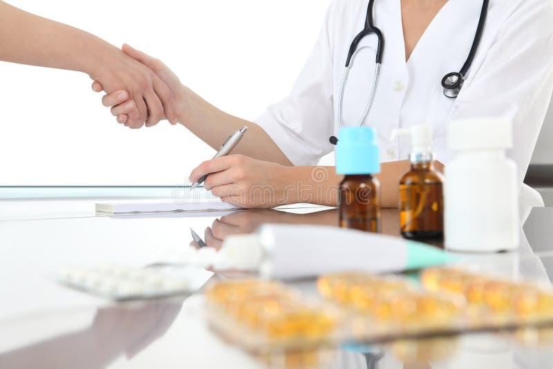 Medico scrive la prescrizione e dare una stretta di mano al suo paziente immagine stock libera da diritti