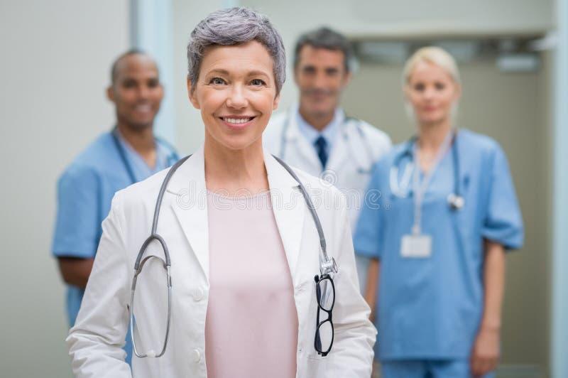 Medico senior con il gruppo immagine stock