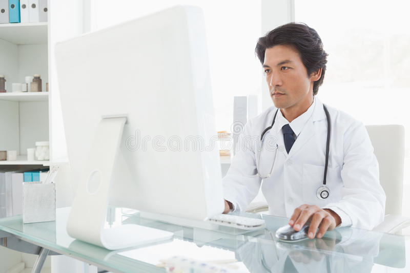 Medico serio che per mezzo del computer immagini stock