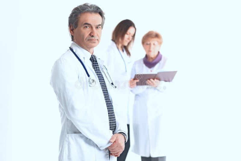 Medico serio del terapista su fondo vago dei colleghi fotografie stock