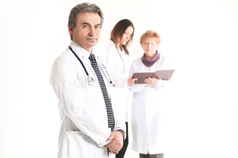 Medico serio del terapista su fondo vago dei colleghi immagini stock libere da diritti