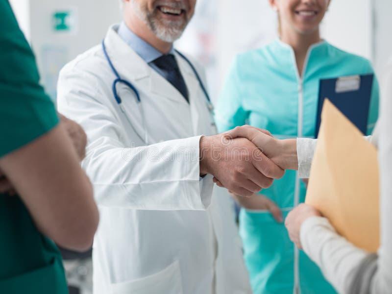 Medico sicuro che stringe la mano paziente del ` s immagini stock