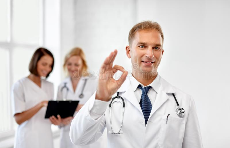 Medico sorridente al segno di approvazione di rappresentazione dell'ospedale immagini stock