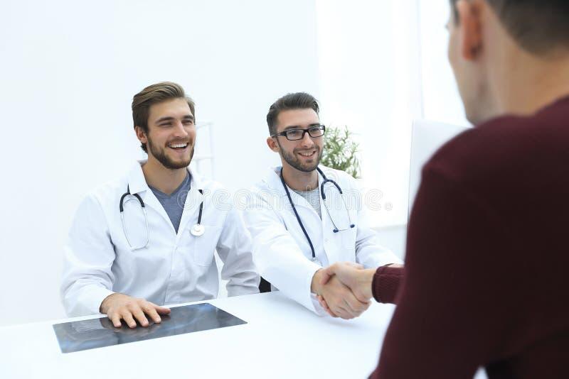 Medico sorridente alla clinica che dà una stretta di mano al suo paziente immagini stock