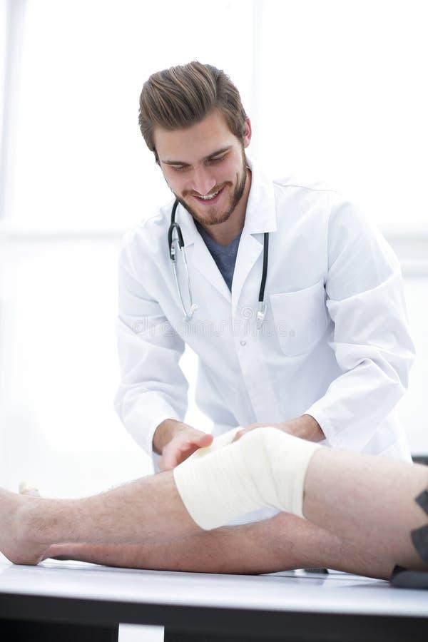 Medico sorridente che esamina la fasciatura sulla gamba paziente del ` s fotografia stock libera da diritti