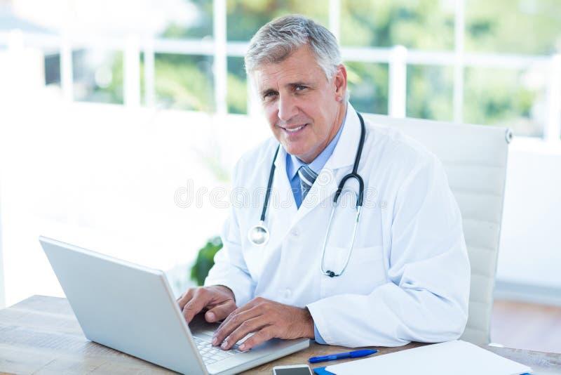 Medico sorridente che lavora al computer portatile al suo scrittorio immagini stock libere da diritti