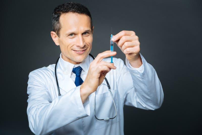 Medico sorridente che posa con la siringa sopra fondo immagine stock