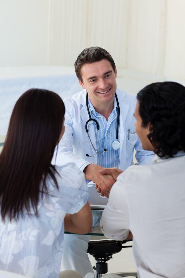 Medico sorridente che spiega diagnosi ad una coppia fotografie stock libere da diritti