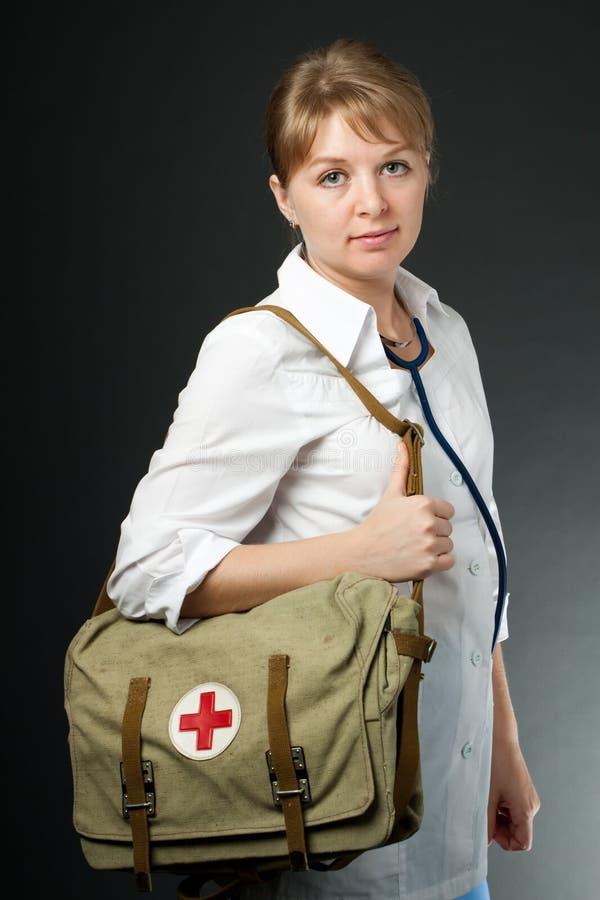 Medico sorridente con il sacchetto del pronto soccorso e dello stetoscopio immagini stock