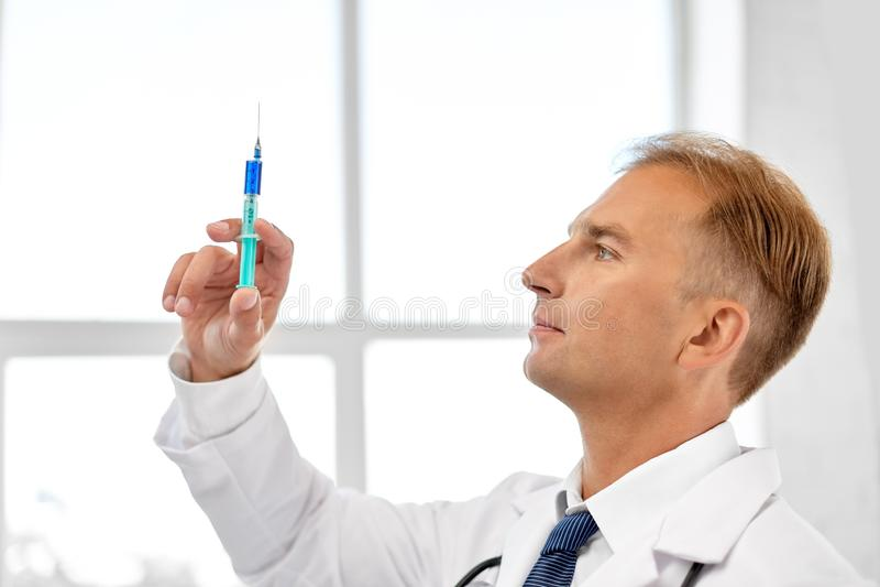 Medico sorridente con la siringa all'ospedale fotografie stock