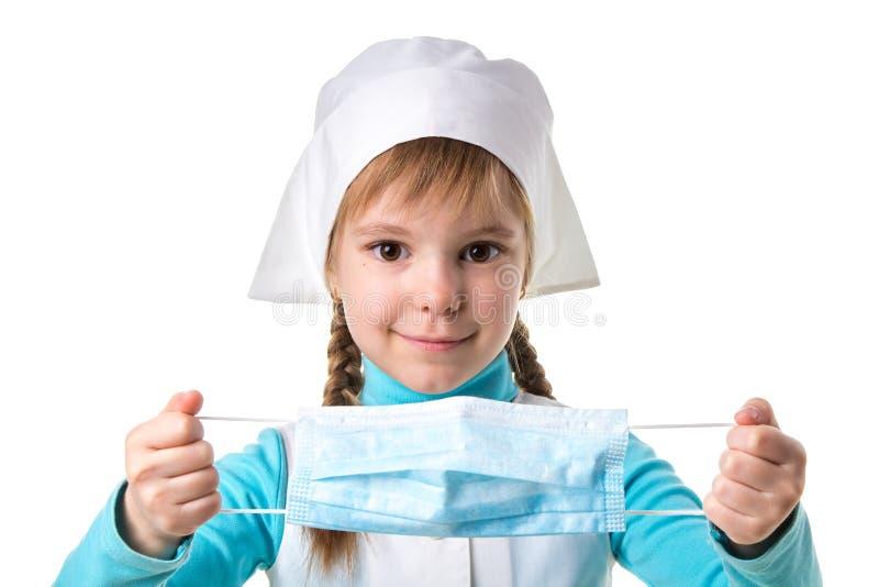 Medico sorridente della ragazza veste una maschera su un fondo bianco del paesaggio fotografie stock