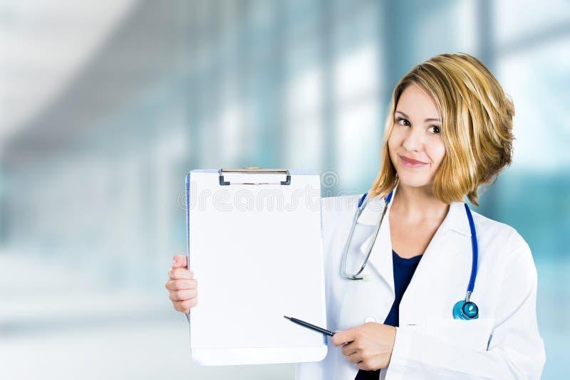 Medico sorridente felice con la lavagna per appunti che sta nel corridoio dell'ospedale fotografie stock