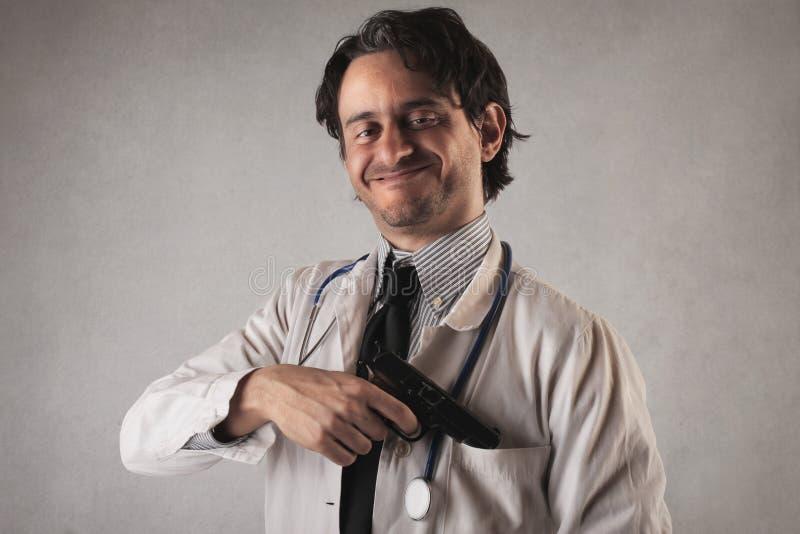 Medico spaventoso con una pistola che esce dalla sua tasca immagini stock