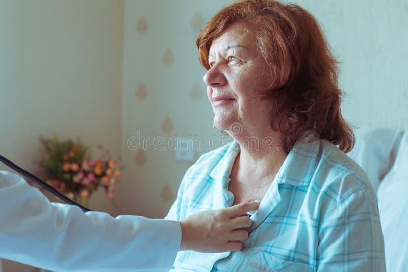 Medico sta controllando il suo vecchio cuore paziente del ` s facendo uso di uno stetoscopio fotografia stock