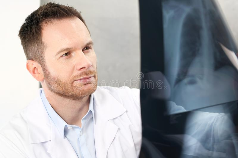 Medico sta guardando i raggi x immagine stock