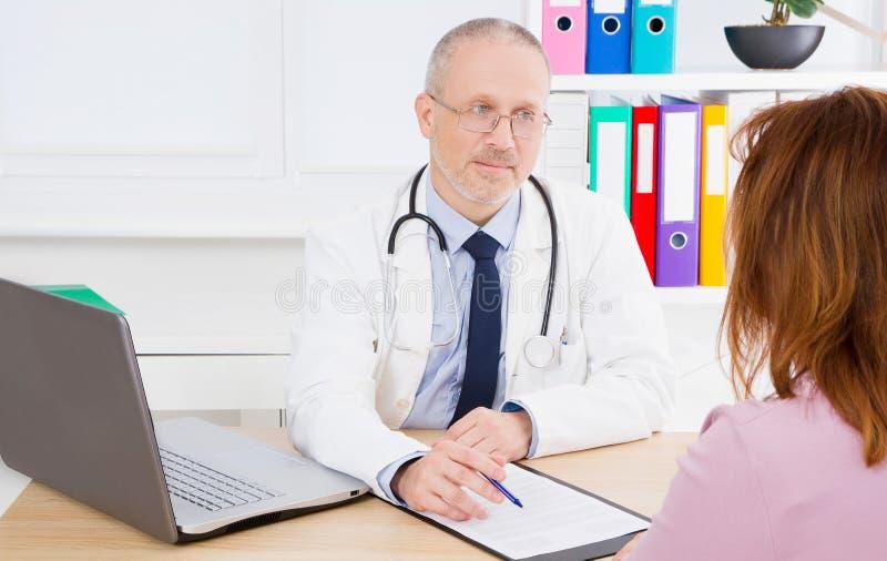 Medico sta parlando con il paziente della donna e sta sedendosi nell'ufficio medico Uomo in uniforme di bianco Assicurazione-mala fotografia stock libera da diritti