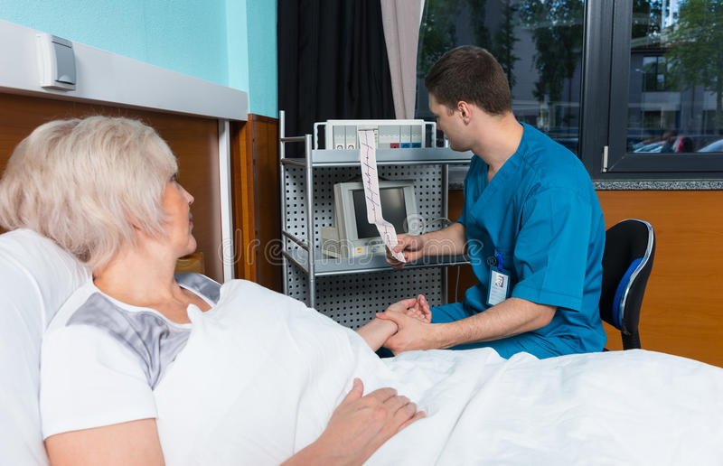 Medico in uniforme sta esaminando l'analisi dell'elettrocardiografo e fotografie stock