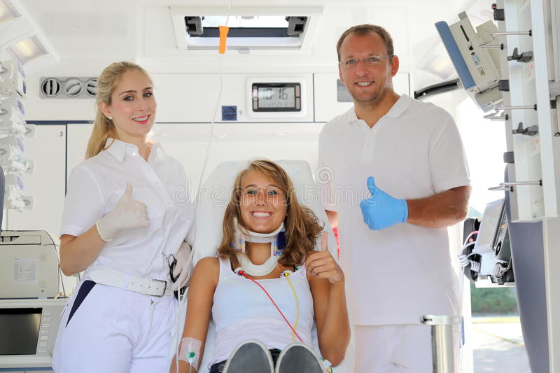 Medics with patient in a Ambulance car happy with thumbs up stock photography