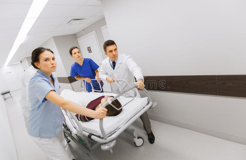 Medics with woman on hospital gurney at emergency stock photo