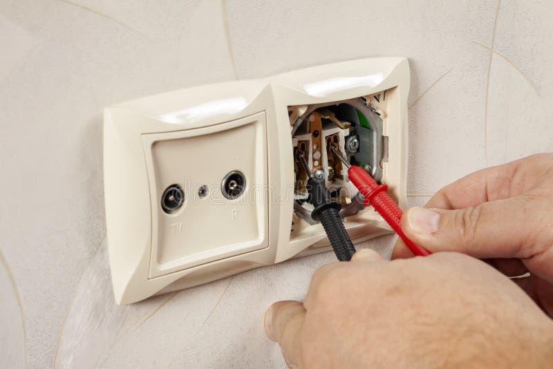 Medida da eletricidade na tomada usando um multímetro à disposição Fotografia de alta qualidade do close-up imagem de stock royalty free
