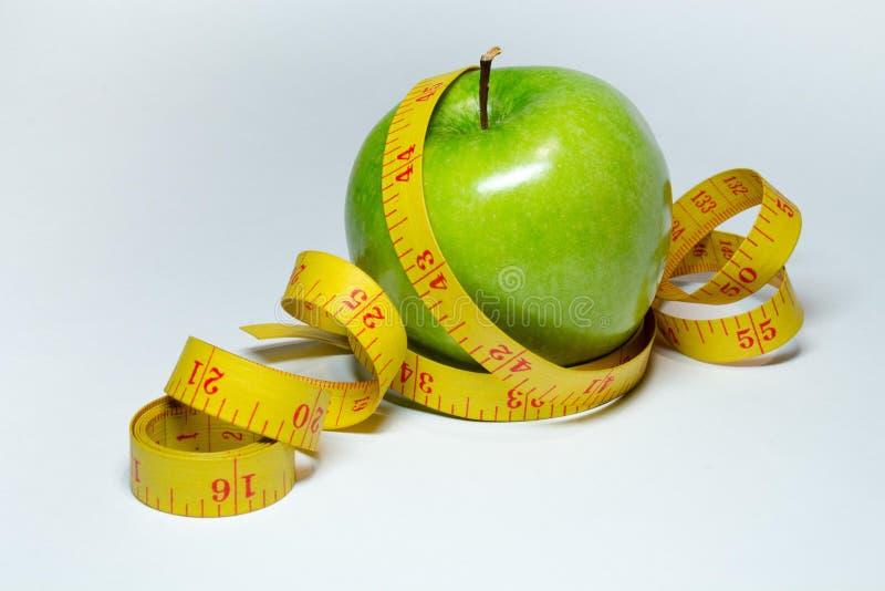 Medida da fita e a maçã isoladas fotografia de stock