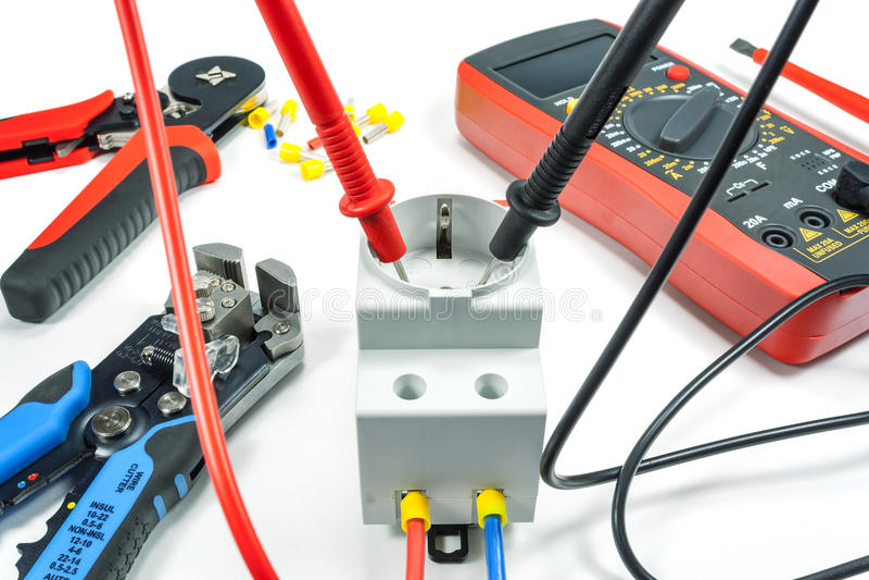 Medida da tensão na tomada elétrica com um multímetro em um fundo branco imagens de stock