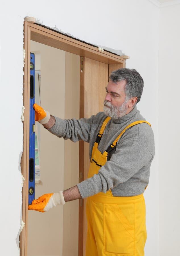 Medida da verticalidade do construtor da porta com ferramenta nivelada fotos de stock