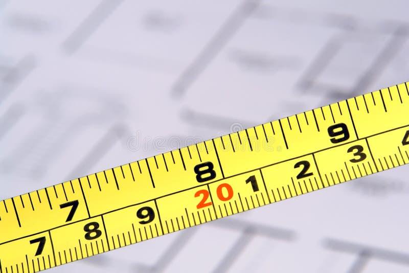 Medida de fita da construção e plantas de assoalho fotografia de stock