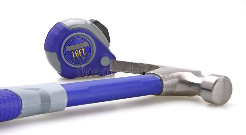 Medida de fita e martelo azul fotografia de stock