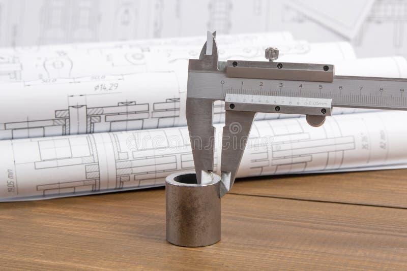 Medida de la pieza de metal con un calibrador en el fondo de los dibujos de ingeniería imagen de archivo libre de regalías