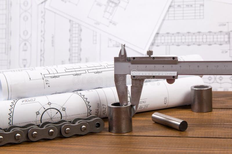 Medida de la pieza de metal con un calibrador en el fondo de los dibujos de ingeniería foto de archivo