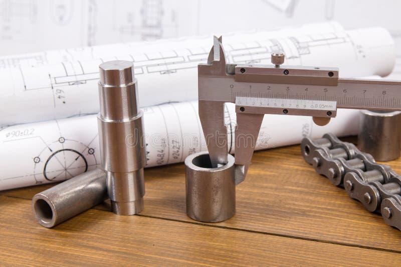 Medida de la pieza de metal con un calibrador en el fondo de los dibujos de ingeniería imagenes de archivo