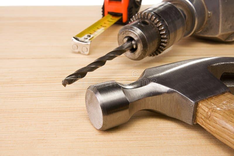 Medida do martelo e de fita na madeira imagens de stock