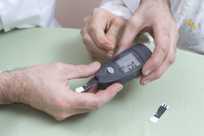 Medida do medidor da glicose com uma mulher adulta As mãos do doutor guardam um glucometer preto imagens de stock