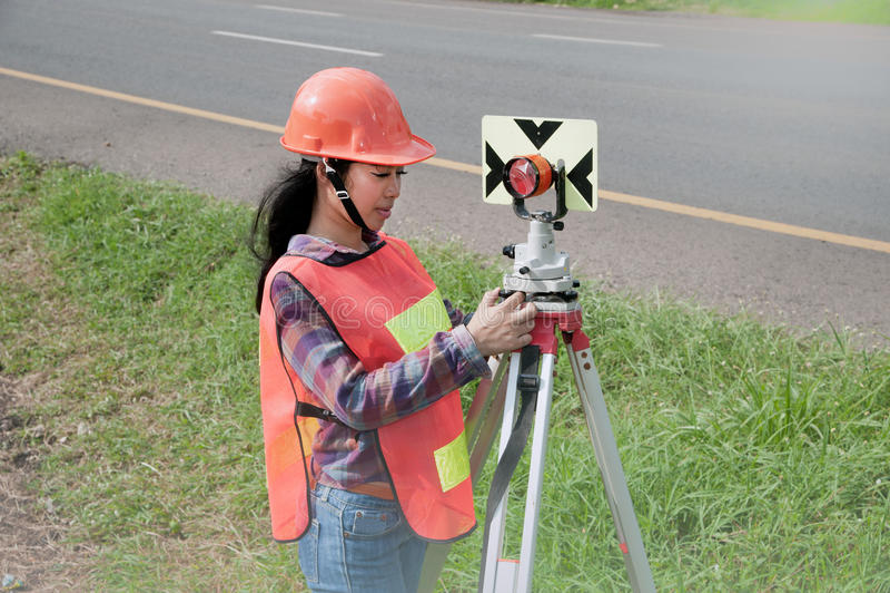 Medida do refletor de prisma do ajuste fêmea do topógrafo ou do coordenador na rua fotografia de stock
