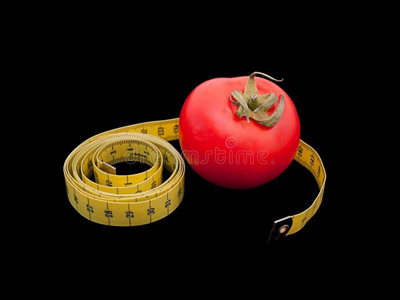 Medida do tomate e de fita sobre o preto fotos de stock