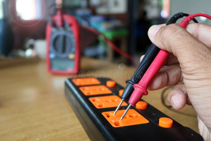 Medida do voltímetro do uso do trabalhador a corrente da tomada da extensão foto de stock