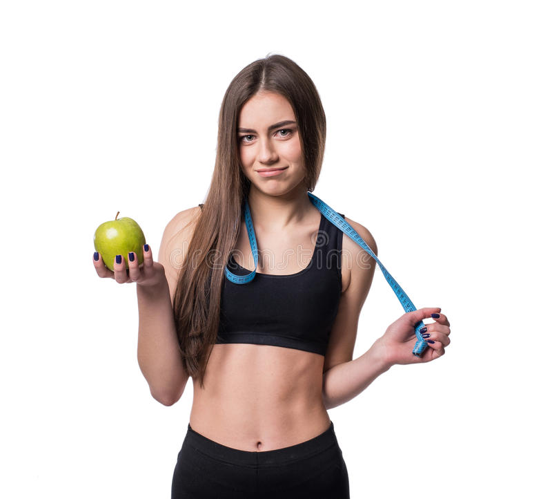 Medida magro e saudável da fita e a maçã da terra arrendada da jovem mulher isoladas no fundo branco Perda de peso e conceito da  fotografia de stock