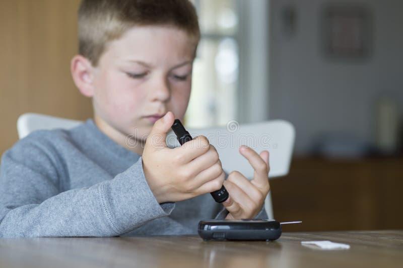 Medida nova do nível da glicose do menino fotos de stock