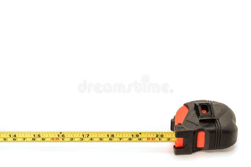 Medida preta e vermelha retrátil da fita da terra arrendada da mão, polegada, isolada no fundo branco imagem de stock