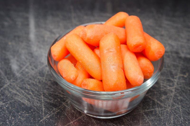 Medida una taza de zanahorias de bebé foto de archivo libre de regalías