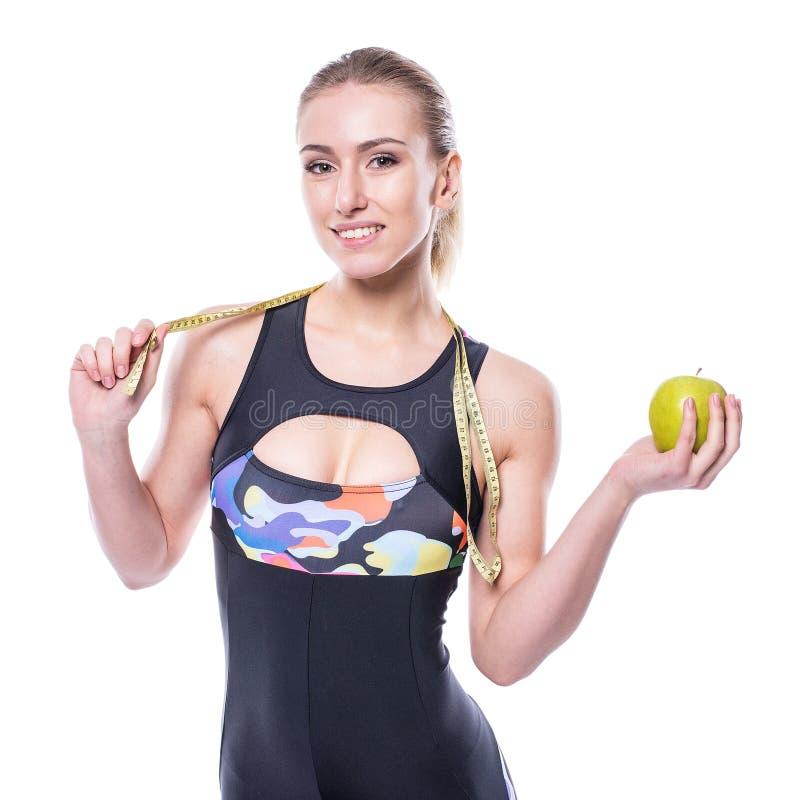 Medida vestindo da fita da terra arrendada do fato de esporte do sportswear da jovem mulher magro e saudável e maçã verde isolada imagem de stock royalty free