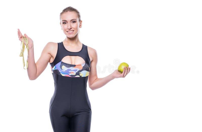 Medida vestindo da fita da terra arrendada do fato de esporte do sportswear da jovem mulher magro e saudável e maçã verde isolada foto de stock royalty free