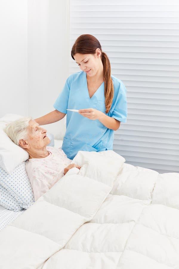 Medidas da febre da enfermeira com idoso imagens de stock