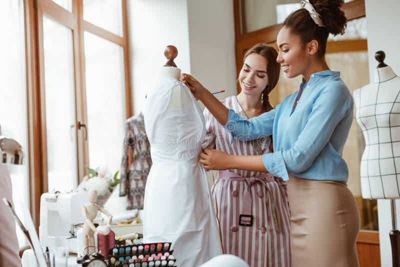 Medidas de ensino da tomada para o vestido novo Duas mulheres no estúdio do projeto foto de stock royalty free