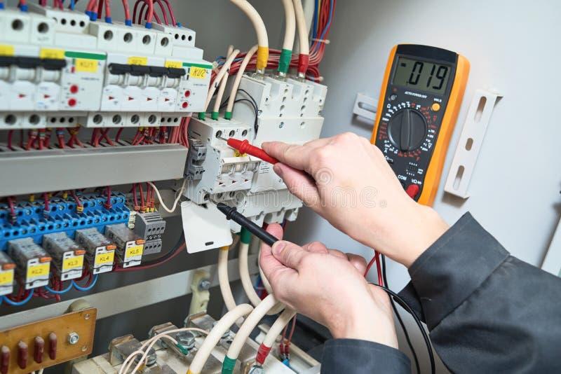 Medidas del electricista con el probador del multímetro imagen de archivo libre de regalías